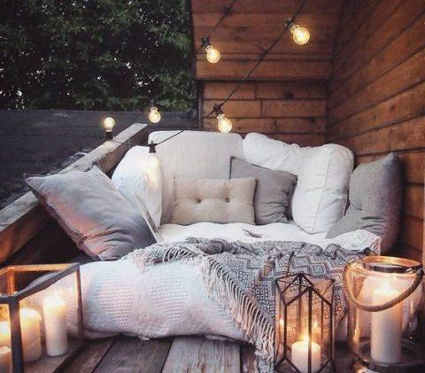 Canapé d'extérieur avec beaucoup de coussins et un très beau plaid