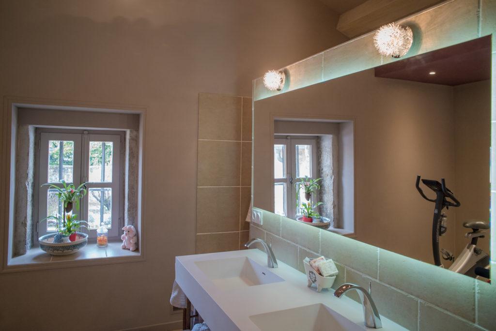 Le miroir de la vasque suspendue revoie la lumière de la fenêtre existante de la salle de bain