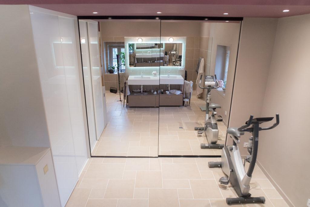 Les miroirs des portes coulissantes renvoient la lumière et agrandissent l'espace de la salle de bain