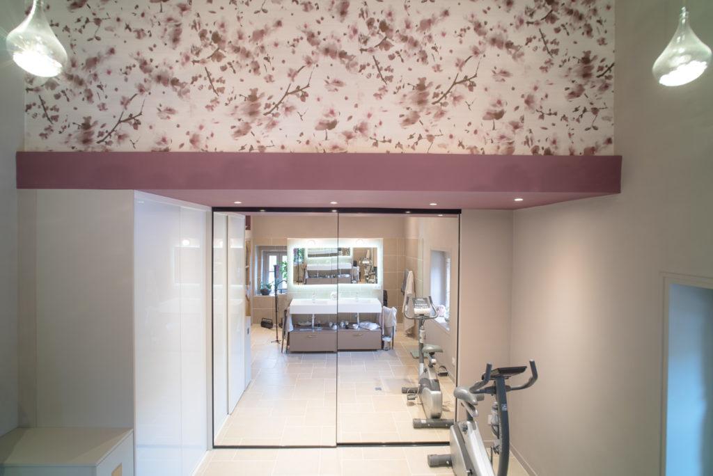 Vue sur la partie dressing de la salle de bain avec des portes coulissante en miroir et un papier peint Elitis